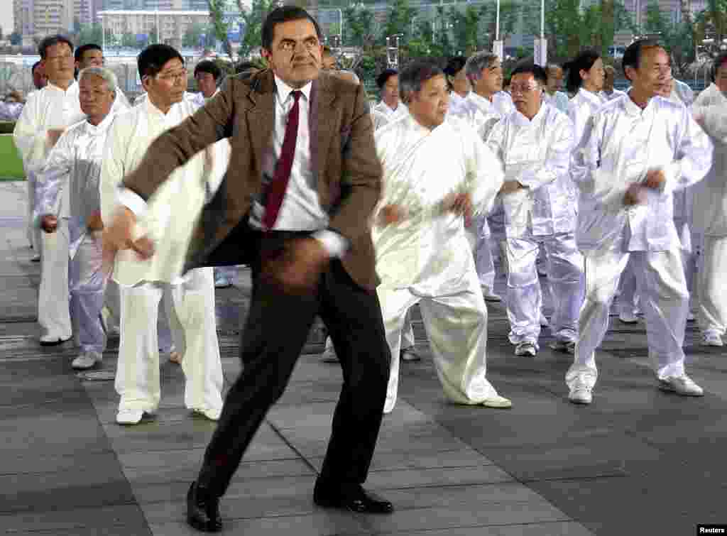 British actor Rowan Atkinson (front), dressed as his popular television character Mr. Bean, dances with Chinese performers during the filming of a promotional video in Shanghai, Aug. 20, 2014.