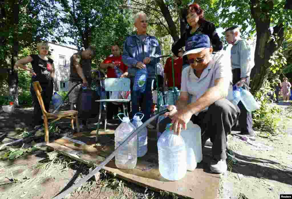 Warga setempat menimba air di Slovyansk, Ukraina Timur (1/7).