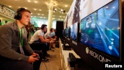 """A gamer plays """"Call of Duty: Advanced Warfare"""" on an Xbox One console during the Xbox Play Day 2014, before the Gamescom 2014 fair in Cologne August 12, 2014. The Gamescom convention, Europe's largest video games trade fair, is opened to the public from A"""