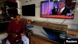 Seorang pedagang di Karachi, Pakistan, makan pagi sambil menonton berita soal Donald Trump. (Foto: Dok)