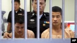 Pekerja migran asal Migran Myanmar Zaw Lin (kiri) dan Win Tun Zaw dikawal oleh polisi setelah dinyatakan bersalah oleh pengadilan Thailand, Kamis (24/12).