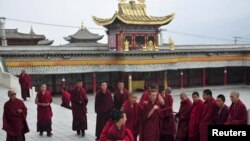Tibetan monks prepare to attend a prayer meeting for tourists at a temple in Huangnan Tibetan Autonomous Prefecture, Qinghai province, China, July 19, 2012.