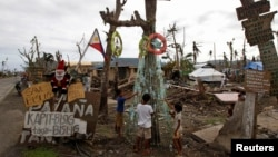 Children, victims of super typhoon Haiyan, decorate their improvised Christmas tree with empty cans and bottles at the ravaged town of Tanuan, Leyte province, central Philippines, Dec. 19, 2013.