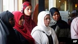 FILE - A group of women listen to Council on American-Islamic Relations-Minnesota Executive Director Jaylani Hussein, speaking about the Somali community concerns about the proposed government-initiated Countering Violent Extremism (CVE) program during a news conference in Minneapolis, Aug. 6, 2015.