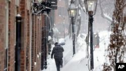 Un hombre con una pala intenta limpiar una acera en Beacon Hill, Boston.