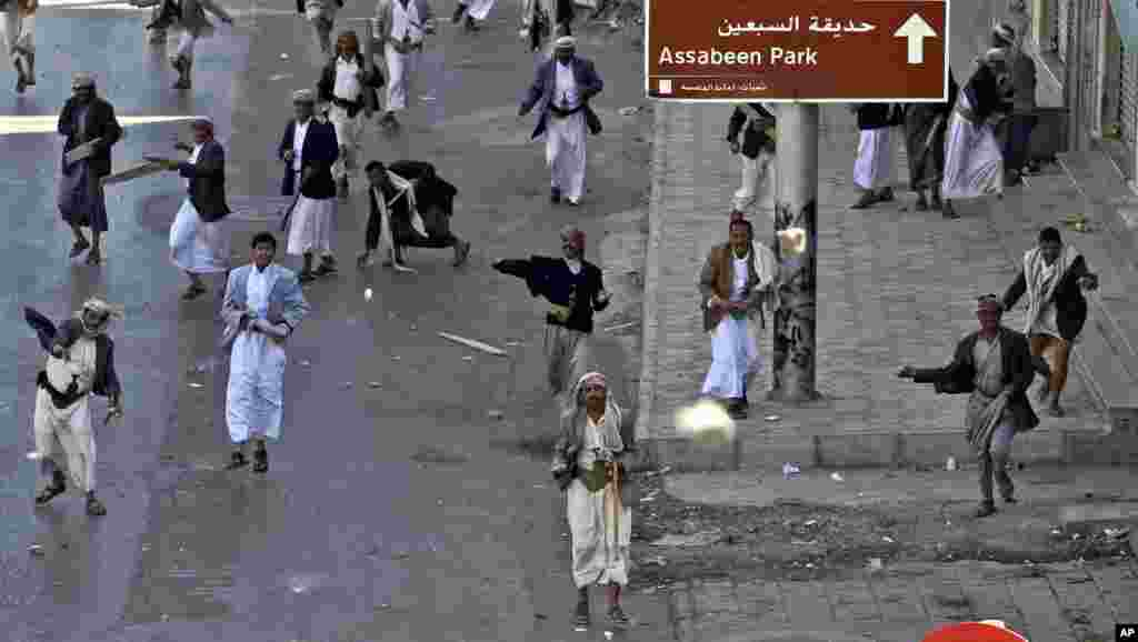 February 18, 2011: Supporters of the Yemeni government hurl stones at anti-government demonstrators, not pictured, during clashes in Sanaa on what organizers called Friday of Rage.