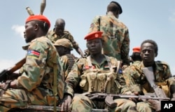FILE - In this photo taken Oct. 16, 2016, a group of South Sudanese government soldiers sit on the back of a pickup truck before visiting the scene of a recent battle in Malakal, South Sudan.