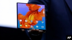 Huawei CEO Richard Yu displays the new Huawei Mate X foldable 5G smartphone at the Mobile World Congress, in Barcelona, Spain, Sunday, Feb. 24, 2019. (AP Photo/Manu Fernandez)