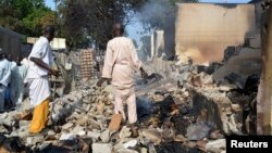 FILE - Two men walk amidst rubble after Boko Haram militants raided Benisheik, west of Borno State capital Maidugur, Nigeria, Sep.19, 2013.