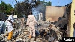 Dua orang berdiri di tengah puing-puing bangunan di wilayah Benisheik, Borno, setelah wilayah itu diserang oleh Militan Boko Haram (19/9/2013).