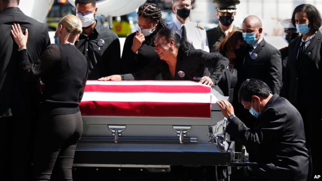 Family members of U.S. Marine Sgt. Johanny Rosario Pichardo are grief stricken upon the arrival of his casket at Logan Airport in Boston.