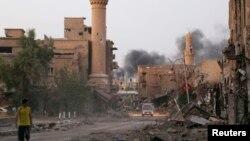 عکس آرشیوی از یک نوجوان سوری که در خیابانی با ساختمان های ویرانه در «دیر الرزور» قدم می زند.