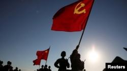 中国解放军军人在内蒙古朱日和训练基地准备参加阅兵,庆祝解放军建军90周年。中共党旗在前,国旗居中,军旗在后(2017年7月30日)