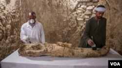 Egyptian excavation workers restore a mummy in a newly discovered tomb in the Draa Abul Naga necropolis on Luxor's West Bank known as KAMPP 150, in Luxor, Egypt, Dec. 9, 2017.(H. Elrasam/VOA)