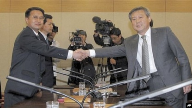 South Korean chief delegate Ryu In-chang, right, shakes hands with his North Korean counterpart Yoon Yong Geun during a meeting to discuss joint research on volcanic activity at the North's highest Paektu mountain, at the Inter-Korean Transit Office in Pa