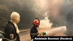 Seorang petugas pemadam kebakaran menggunakan selang air saat kebakaran hutan terjadi di Desa Ain al-Hammam di wilayah Tizi Ouzou, timur Aljir, Aljazair, 10 Agustus 2021. (Foto: REUTERS/Abdelaziz Boumzar)