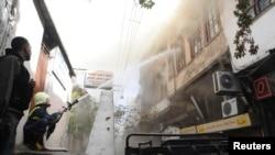 Petugas berusaha memadamkan api akibat tembakan mortir pemberontak di Damaskus, Suriah hari Selasa (15/10).