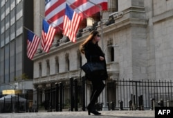 FILE - A person walks past the New York Stock Exchange (NYSE) at Wall Street on November 16, 2020 in New York City.