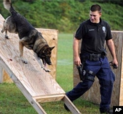 In this undated photo released by the Hattiesburg Police Department, Officer Benjamin Deen participates in K-9 training at the police academy in Hattiesburg, Miss.