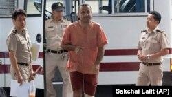 Atris Hussein, center, a Lebanese-Swedish citizen, arrives at criminal court in Bangkok, Thailand, Sept. 18, 2013.