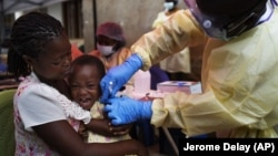 In this Saturday, July 13, 2019 photo, a child is vaccinated against Ebola in Beni, Congo.