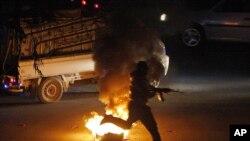 Şam'daki çatışmalarda elinde kalaşnikofuyla görüntülenen bir Suriyeli isyancı
