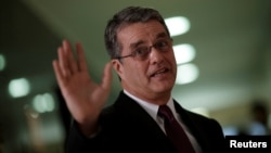 FILE - Roberto Azevedo, director-general of the World Trade Organization, gestures during a news conference in Brasilia, Brazil, March 12, 2018.