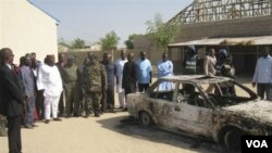 Warga Nigeria mengelilingi sebuah mobil yang terbakar akibat pemboman yang memicu bentrokan antarkelompok bersenjata Kristen dan Muslim.