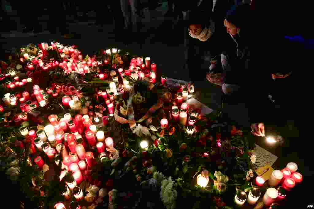 People light candles at a makeshift memorial in front of the Kaiser-Wilhelm-Gedaechtniskirche (Kaiser Wilhelm Memorial Church) in Berlin, where a truck crashed into a Christmas market.