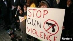 """12月19日在洛杉矶市政厅前举行的烛光守夜活动中,人们举着""""制止枪击暴力""""的标语牌"""