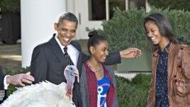 """Prezidan Barack Obama avèk 2 pitit fi li Sasha (adwat) ak Malia. Li swiv yon tradisyon nan okazyon Thanksgiving nan lè li bay 2 kodenn yon """"padon prezidansyèl"""" ( 21 novanm 2012)."""