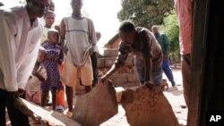 Des survivants d'un séisme qui a frappé l'est de l'Afrique constatent les dégâts sur leur maison à Kalémie, République démocratique du Congo, 7 décembre 2005.