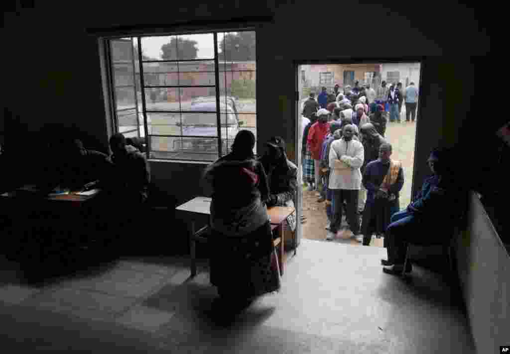 Zimbabweans line up to cast votes in the country's general elections in Morondera, July 31, 2013.