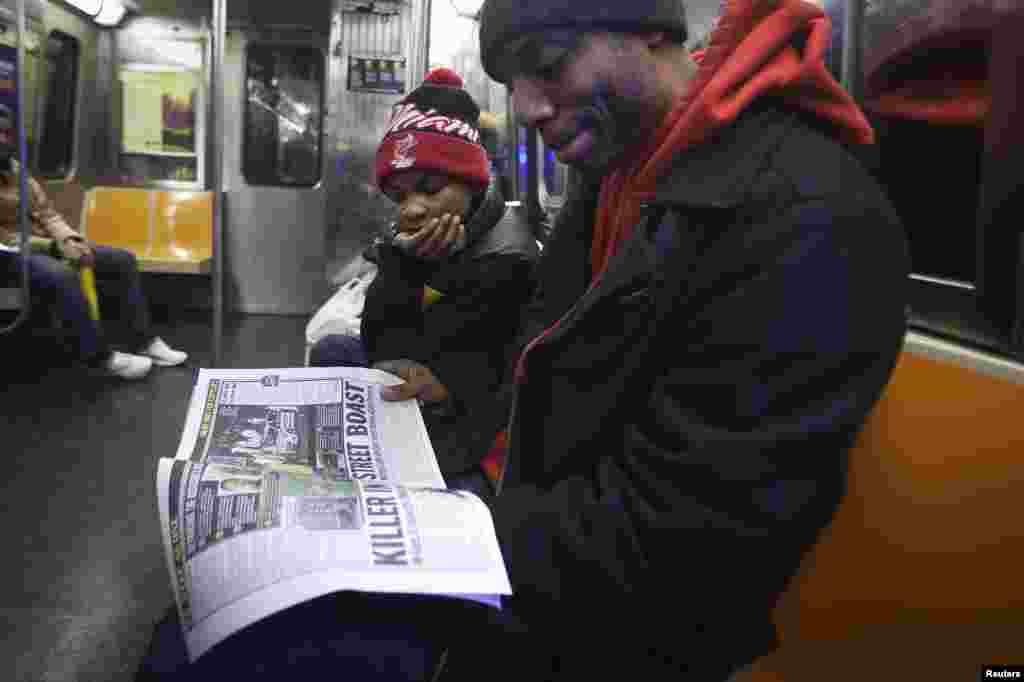 Daniel Mitchell talks with his son Daniel Mitchell 2nd about the death of two police officers who were fatally shot in the Brooklyn borough, as they read a local paper on the G train in New York, Dec. 22, 2014.