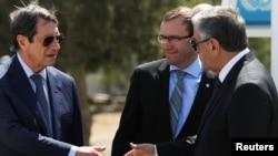 FILE - Greek Cypriot leader and Cyprus President Nicos Anastasiades, left, shakes hands with Turkish Cypriot leader Mustafa Akinci as U.N. envoy Espen Barth Eide looks on, in the buffer zone of Nicosia airport, Cyprus, Sept. 14, 2016.