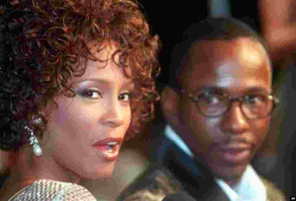 """FILE - In this Oct. 13, 1997 file photo, Whitney Houston looks over her shoulder as her husband Bobby Brown looks to her at the premiere of """"The Wonderful World of Disney"""" movie """"Cinderella,"""" at Mann's Chinese Theater in the Hollywood section of Los Angel"""