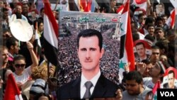 Medios de comunicación estatales reportaron que multitudes ondean banderas sirias a favor de Assad.