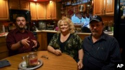 From left, Daniel J. Moore, Lisa Moore and Daniel E. Moore pose for a picture at their kitchen table in Newton Falls, Ohio, Monday, May 1, 2017.