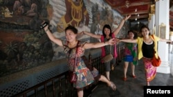Chinese tourists pose for a picture inside the Grand Palace in Bangkok, May 24, 2014.