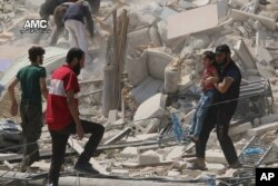 FILE - This photo provided by the Syrian anti-government activist group Aleppo Media Center (AMC), shows a Syrian man carrying a girl away from the rubble of a destroyed building after barrel bombs were dropped on the Bab al-Nairab neighborhood in Aleppo,Syria.