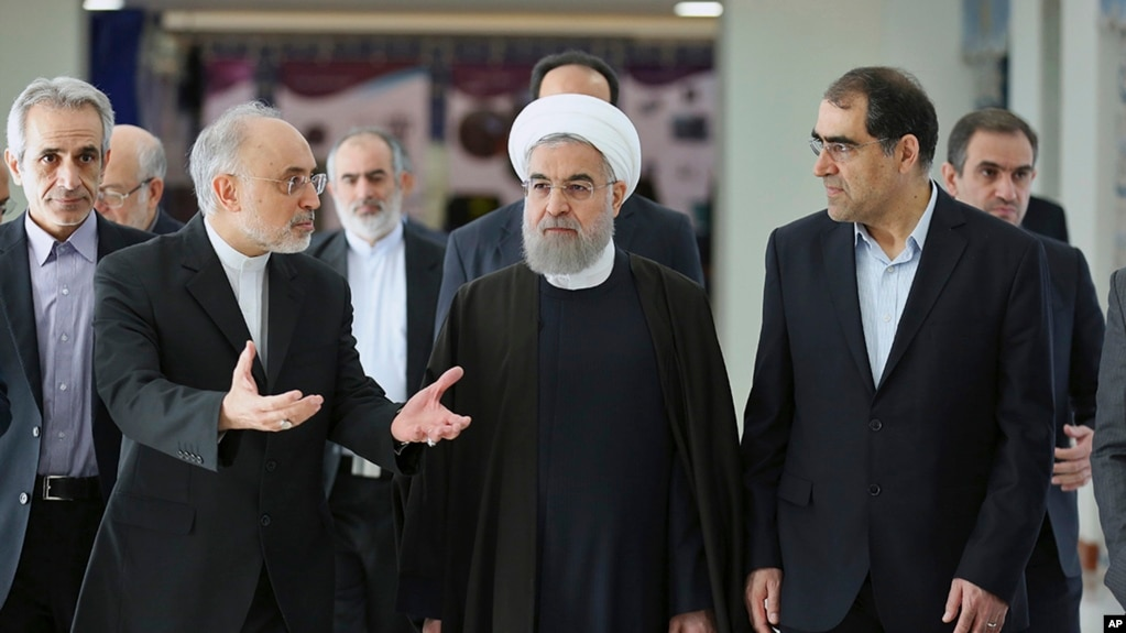 FILE - President Hassan Rouhani (center) listens to head of Iran's Atomic Energy Organization Ali Akbar Salehi (left) while attending a ceremony marking the national day of nuclear technology in Tehran, Iran, Thursday, April 7, 2016. Iran's Health Minister Hassan Ghazizadeh Hashemi is at right.