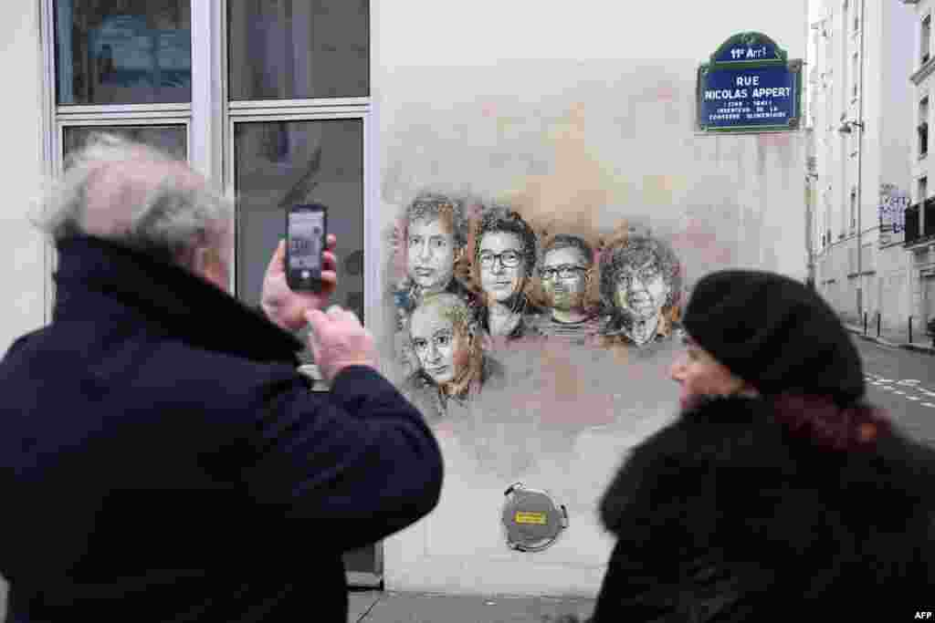A man takes a picture of portraits (LtoR) of late French satirical weekly Charlie Hebdo's deputy chief editor Bernard Maris, French cartoonists Georges Wolinski, Bernard Verlhac (aka Tignous), Charlie Hebdo editor Stephane Charbonnier (aka Charb) and Jean Cabut (aka Cabu) near the magazine's offices at Rue Nicolas Appert, in Paris on the third anniversary of the jihadist attack on French satirical magazine Charlie Hebdo.