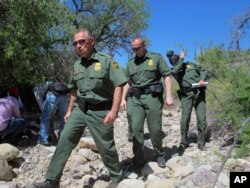 FILE - U.S. Border Patrol Tucson Sector Chief Manuel Padilla, left front, walks with other agents and media during a tour in the Buenos Aires National Wildlife Refuge near Sasabe, Arizona.