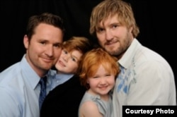 Stay-at-home dad Blake Humphreys (R) with his partner Paul Larsen (L) and their two children Aiden and Camille.