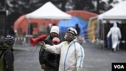 Petugas di Fukushima mengenakan baju khusus anti-radiasi, Selasa (15/3).