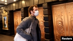 FILE - A man in a protective mask walks past a closed theatre after it was announced that Broadway shows will cancel performances due to the coronavirus outbreak in New York, U.S., March 12, 2020. (REUTERS/Mike Segar/File Photo)