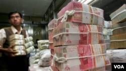 Seorang pekerja di Bank Indonesia mengatur tumpukan mata uang Rupiah (foto: dok). Nilai tukar rupiah terhadap dollar Amerika melemah minggu lalu, namun diperkirakan akan kembali menguat.