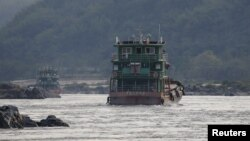 In this file photo, Chinese cargo ships sail on the Mekong river near the Golden Triangle at the border between Laos, Myanmar and Thailand March 1, 2016.