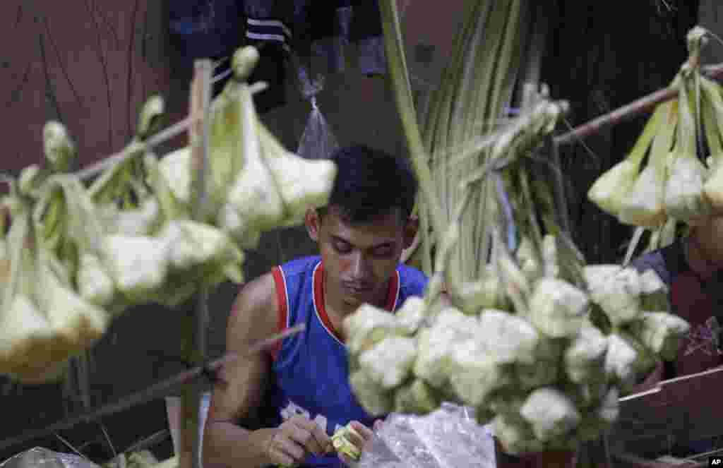 Seorang pedagang membuat kulit ketupat sambil menunggu pelanggan menjelang Idul Fitri di Jakarta, Selasa, 4 Juni 2019. (Foto: AP)