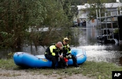 Members of a combined New Bern/Greenville swift water rescue team Brad Johnson, left, and Steve Williams rest after searching for people stranded by floodwaters caused by the tropical storm Florence in New Bern, N.C., Sept. 15, 2018.